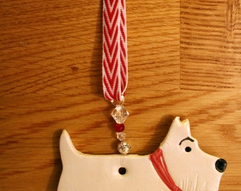 White West Highland Terrier Dog with a lovely red collar. Handmade pottery sent to you in a lovely gossamer bag ready to be given as a gift.