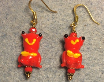 Reddish orange and yellow lampwork frog bead earrings adorned with red Chinese crystal beads.