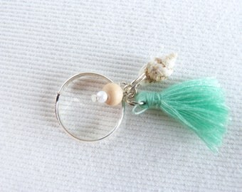 Ring was wooden beads, pastel green PomPoms of water, pearls and shells