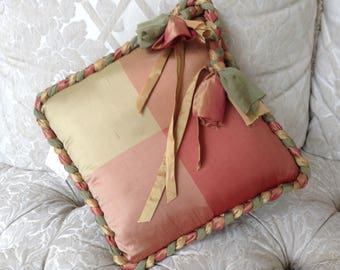 Pink and gold cushion cover with braided edge. Made with furnishing fabric
