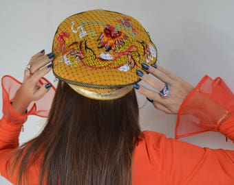 Yellow beret with Chinese dragon figure.