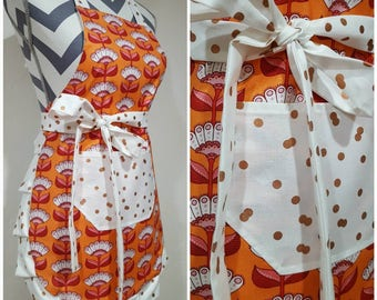 Youth/child's apron. Girl's apron. Fun red/pink/white flowers with orange on main.  Rose gold polka dots on pocket, ties ands frills.