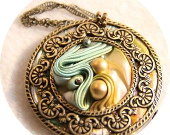 Collier médaillon en soie shibori bleu ivoire et contour bronze, collier textile en soie ivoire et bronze, collier bleu en soie et cristal