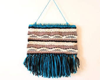 Neutral woven wall hanging with a pop of color