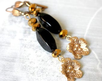 Black and gold sleeper earrings small flower.