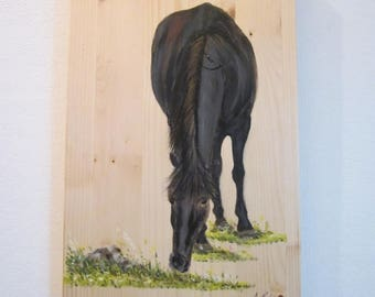 Black horse in a meadow painting on wood