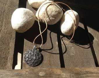 Beautiful necklace of genuine leather with chic antiqued silver pendant that will enhance your neckline.