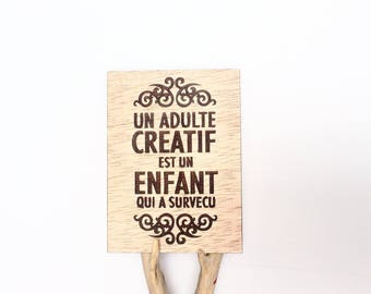 "Nice card ""a creative adult is a child who survived"" original wooden realization: Laser made in france"