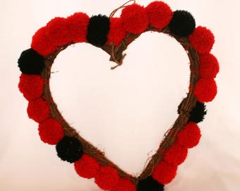 Handmade, black and red large pom poms, with a slight sparkle, attached to a large wicker hanging heart