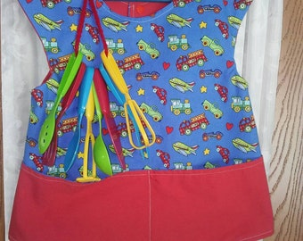 Girls or boys 5T apron. Two pocket. Planes, trains, automobiles on blue background.  Comes with 8 colored cooking play utensils.