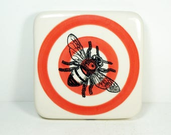 porcelain art tile / trivet with a bee print on red-orange bullseye. ready to ship