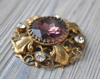 Vintage filigree brass brooch with glass rhinestones.