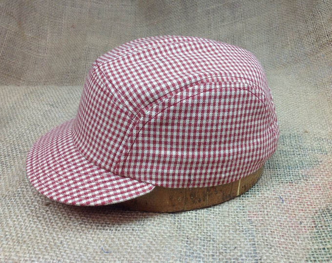 "Gingham check 5 panel cap, brushed cotton sweatband, adjustable with leather strap and brass slide. Visor size shown is 2"". Other visors ava"