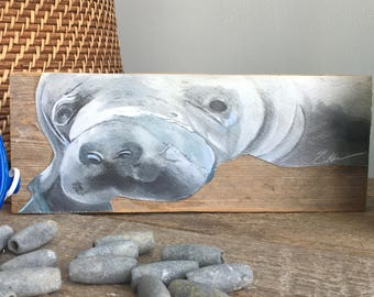"""Hand painted manatee on reclaimed, stackable wood. Art that stands on its own. This sweet manatee is 4"""" x 10""""."""