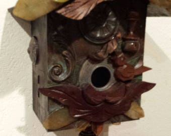 One of a Kind Up-Cycled Cuckoo Clock Bird House. Made with Cuckoo clock parts, carved Glass leaves,safety opening,vtg finial. Indoor or out.