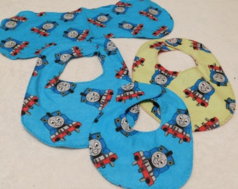 newborn baby bib and burp cloth set made from blue or lime green Thomas the Train flannel with blue camo or red heart backing