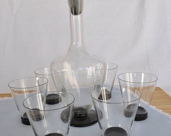 Glasses service with transparent glass bottle and black years ' 50