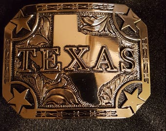 In stock,  hand engraved trophy buckle with shape of Texas and the word TEXAS