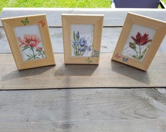 Three embroidered flowers each in his own frame
