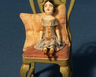 12th scale model of a dolls house toy doll on a chair