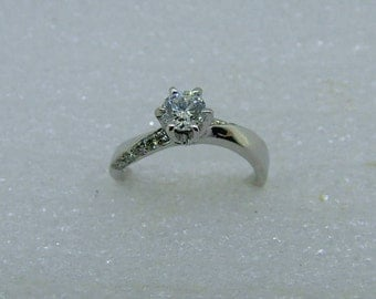 solitaire, engagement ring in 18 carat white gold. 0.45carat centre diamond surrounded by 0.20 points diamonds