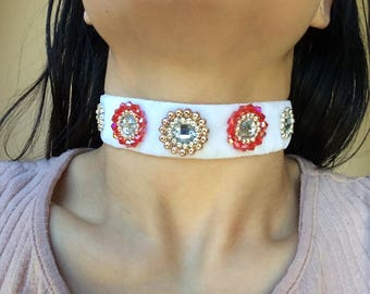 A white velvet choker with red, silver and rose gold beads. Includes shiny gems in the centre.