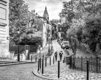 Montmartre walk from the Sacre coeur in black and white on cobblestone in Paris, France.