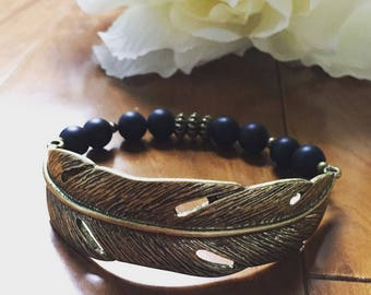 Feather Accent Stretch Bracelet. Black and Antique Crass Stretch Bracelet. Feather Cuff Bracelet. Boho. Chic. Sugarplum Gallery.