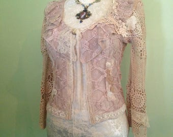 Cream lace jacket adorned with Handmade silk roses and vintage or antique lace embellishments.