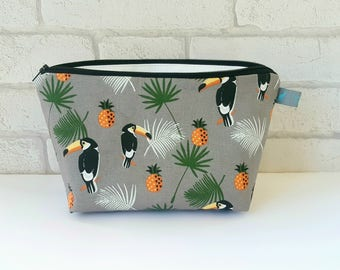 Tropical Toucan Makeup Bag with palm leaves and pineapples on grey background
