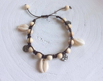 Knotted bracelet with wooden beads, cowry shells and Bronze charms