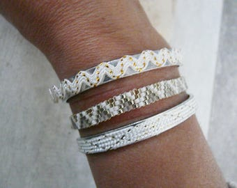 Together of 3 white bracelets and gilt, weaved bracelet and cuffs(headlines)