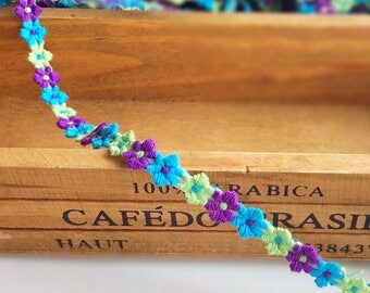 Very pretty three colour mock embroidered daisy flower trim in purple, lime and turquoise. Per metre