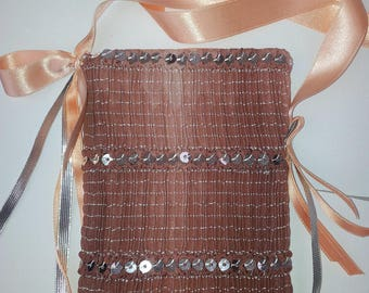 Praline, this phone case has wear around the neck in salmon and bubbled and sequined satin lined with satin