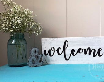 grey-washed welcome sign
