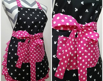Youth apron. Girl's apron. Black with white mickey heads on main.  Pink with white polka dots on pocket, ties and frills.