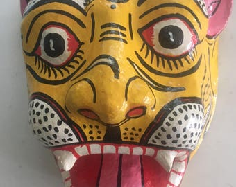A large papier mache tiger head with mouth open in a roar wall hanging