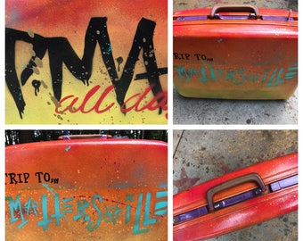 """Hand painted """"Trip to Mattersville"""" vintage upcycled suitcase."""
