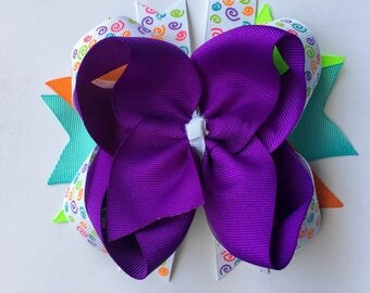 Purple Boutique Bow with Printed Swirls of Lime Green, Aqua, Orange, Pink and Lime Green on Surround. Aqua, Green and Orange Spikes