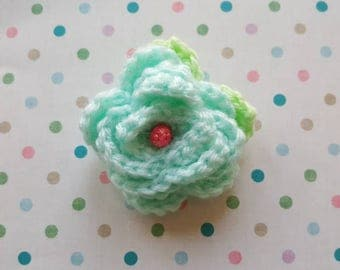 Beautiful crochet flower brooch with pale green leaves and sparkling pink bead center detail.