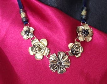 Necklace of metal flowers and black stones.