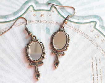 A pretty pair of earring mirror, vanity hand mirror