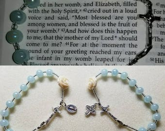 Light Blue 1 Decade Rosary Bracelet w/carved acrylic White Rose and Silver plated St Benedict Crucifix.