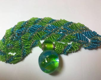 Kim Miles blue and green glass focal bead on a Dutch spiral beaded chain with magnetic clasp