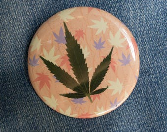 Pressed Cannabis Leaf Button on Orange, Yellow & Purple Background