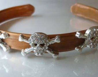 Queen of the Night is a copper cuff bracelet with three skull and crossbones that wil add a little bling to your wrist