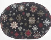 Oval placemat with snowflakes on black with red scroll design on reverse, set of 4
