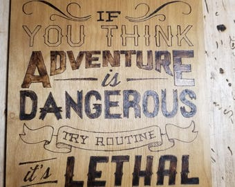 Adventure is dangerous typography done in pyrography