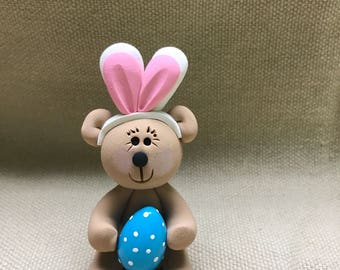 Bear with bunny ears holding Easter egg