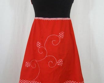 Red and black knee-length dress and flower in relief